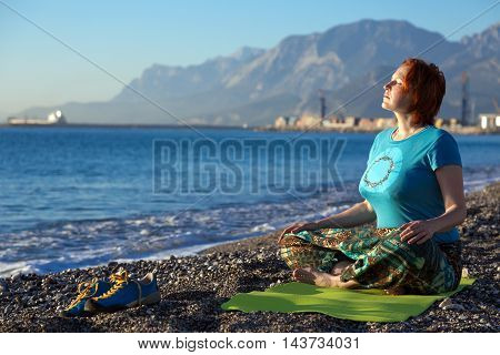 Young Woman meditating on rocky Ocean Beach sitting on green Yoga Mat sporty Shoes staying apart Coast and Mountains on Bacgkround