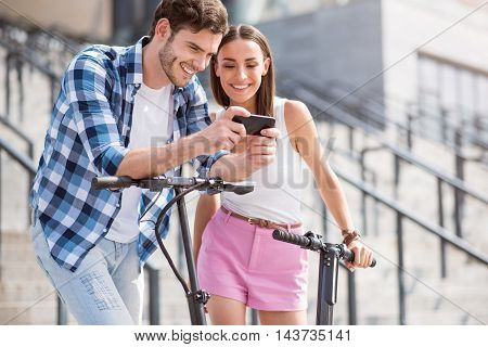 Digital time. Positive delighted friends smiling and using cell phone while standing near scooters