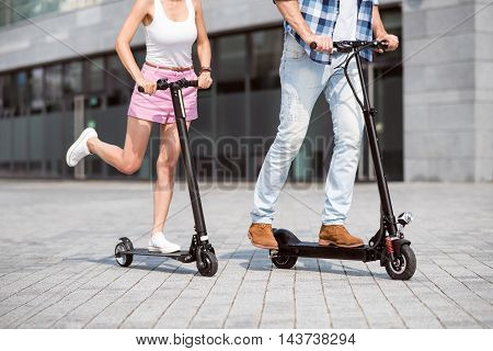 Activate your life. Pleasant friends using scooter and riding while resting together