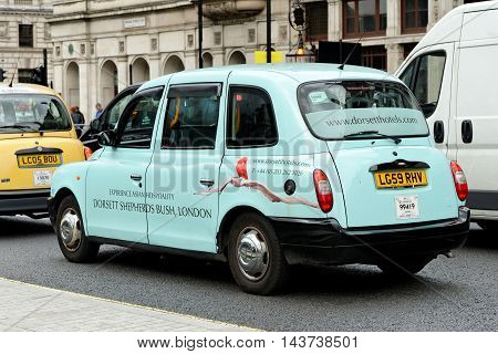 LONDON UK - JULY 8 2016: A taxi on a central street in London. Motorized hackney cabs in the UK are known as black cabs although they are now produced in a variety of colours.