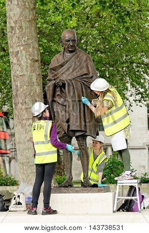LONDON UK - JULY 8 2016: Mahatma Gandhi statue on Parliament square being polished. It was unveiled in march 2015 to mark the 100th anniversary of his return to India to struggle for independence from British rule.