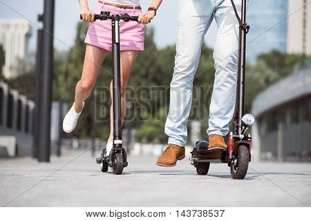 Nice time spending. Pleasant friends using scooter while riding it and resting together