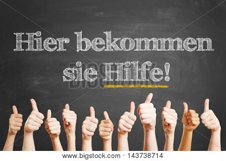 "German Positive help text ""Hier bekommen sie Hilfe!"" (Here you get help!) written on a blackboard with chalk"