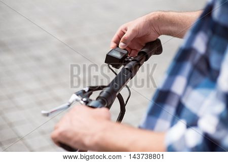 Check it out. Close up of hands of pleasant man holding handle of scooter and riding it