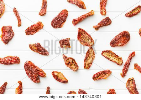 Tasty dried tomatoes on white table.