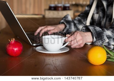 Person working on Computer drinking Coffee at wooden Table with Fruits Pomegranate and Orange on foreground