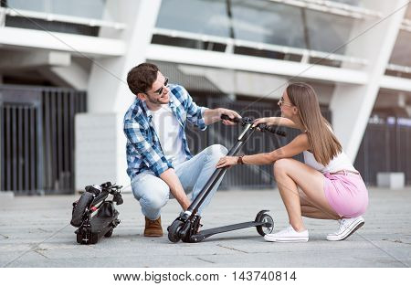 I will help you. Positive delighted friends holding kick scooter and smiling while spending free time together