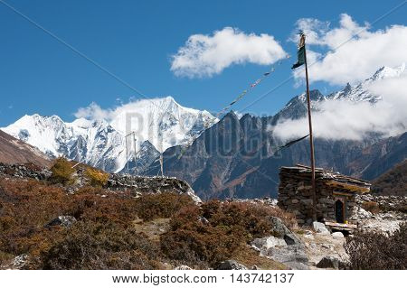 Prayer flags and wheels in Langtang Valley with Langshisa Peak (Langshisha Ri) on background Langtang National Park Rasuwa District Bagmati Nepal.