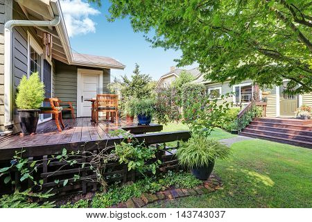 View Of Guest House With Wooden Deck And Nicely Trimmed Garden