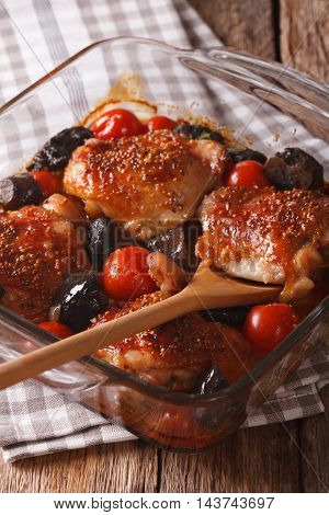 chicken thigh baked with tomatoes and cep mushrooms close up in baking dish on the table. vertical poster