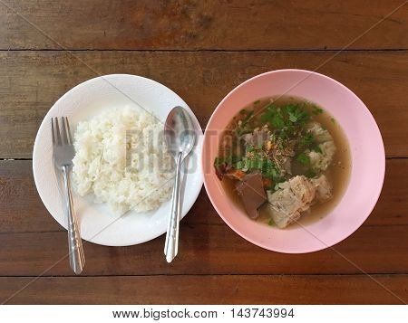 soup and rice. Hot soup with pork on wooden table.