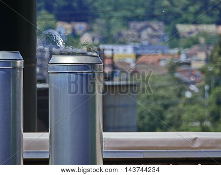 Industrial chimney with flackering hot air on industrial building