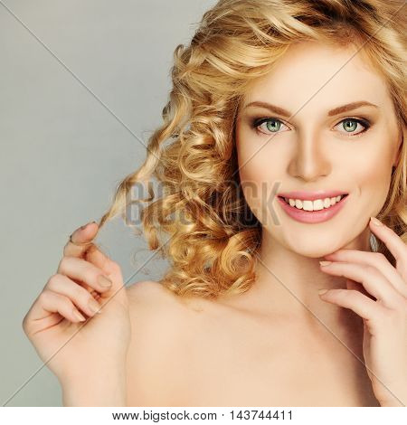 Blond Curly Hair Girl. Beautiful Smiling Woman Touch her Hair Curl