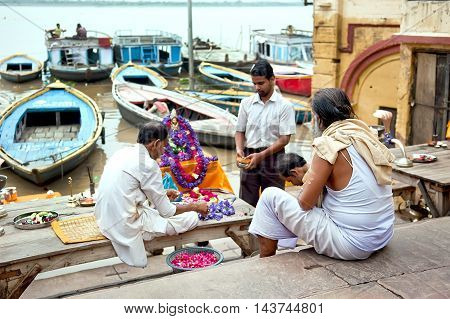 Varanasi Uttar Pradesh India - July 30, 2011: Unidentified Hindu pilgrims preparing for the Ganga Aarti ritual. Puja is a Hindu ritual that takes place at Triveni Ghat on the banks of the river Ganges