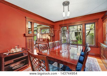 Red Walls In Dining Room. Burgundy Wooden Table With Carved Chairs