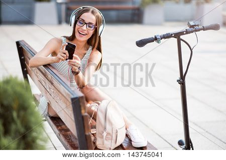 Joyful mood. Cheerful beautiful smiling woman sitting on the bench and using cell phone while listening to music