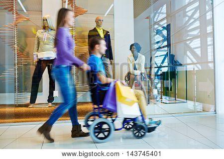 Woman Pushing Wheelchair Husband in Mall
