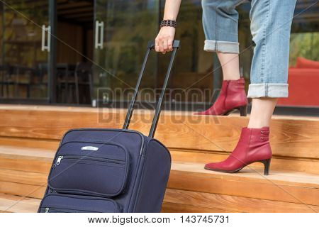 Person walking up on wooden Stairs pulling Travel Suitcase female Legs and Hand casual vacation Clothing red attractive high Heels Shoes and Jeans