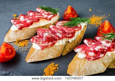 Sandwiches with salami tomato and dill on a dark background.