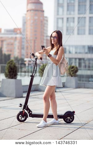 My extraordinary ordinary days. Positive smiling beautiful woman using cell hone and standing near kick scooter while expressing joy