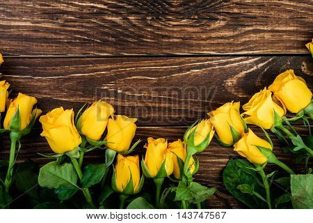 Yellow roses over  wooden table. Floral background.