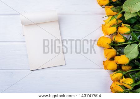 Yellow roses and paper on white wooden table
