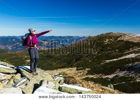 Female Hiker standing on snowy Rocks admiring scenic Winter Mountain View carrying Backpack and walking Pole