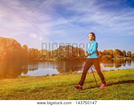 Nordic walking adventure and exercising concept - woman hiking withnordic walking poles in park. With light leak and lens flare