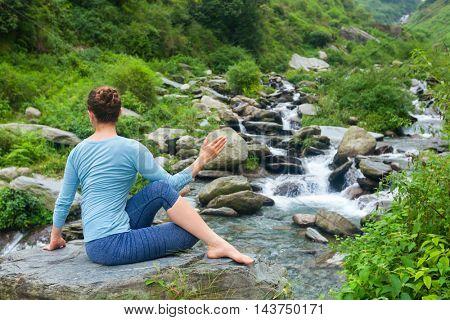 Yoga exercise outdoors -  woman doing Ardha matsyendrasanaasana asana - half spinal twist pose at tropical waterfall in Himalayas in India