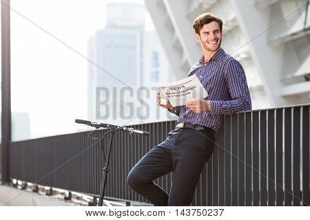 Modern citizen. Cheerful delighted handsome man drinking coffee and reading newspaper while standing near kick scooter