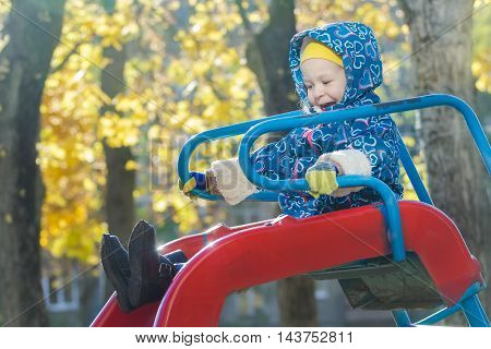 Laughing girl in warm hooded jacket is sliding down red plastic playground slide at yellow autumn tree leaves background