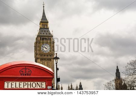 Red telephone booth front of Big Ben on a cloudy day London England