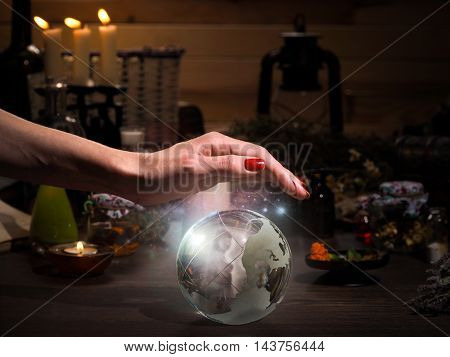 Female hand on the magic sphere. Silhouette of a ghost in a bowl. Flasks retort for alchemy. Concept - occult esotericism spiritualism calling the spirits and ghosts underworld