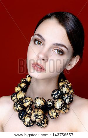 Portrait of pretty young woman with beads on red background