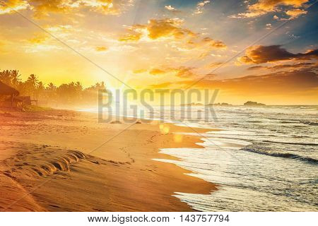 Beach resort vacation holidays background - tropical sunset on ocean beach. Sri Lanka. With light leak and lens flare