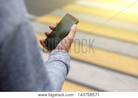 Closeup of mans hand holding phone with blank screen on pedestrian crossing. Image with lens flare effect