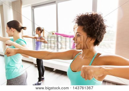 fitness, sport, training, people and martial arts concept - group of happy women working out fighting stance in gym