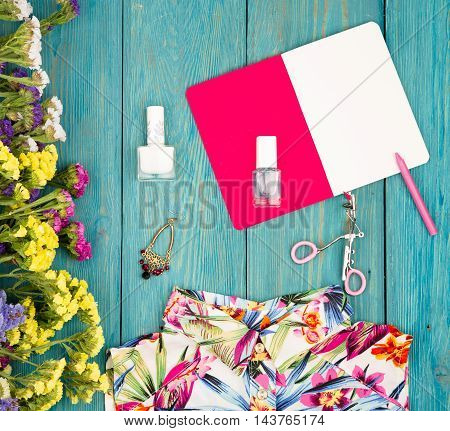 Dress, Colorful Flowers, Cosmetics Makeup, Notepad, Bijou And Essentials On Blue Wooden Background