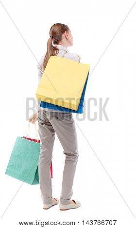back view of woman with shopping bags. backside view of person.  Rear view people collection. Isolated over white background. Skinny girl in white denim suit is throwing shopping bags on her back.