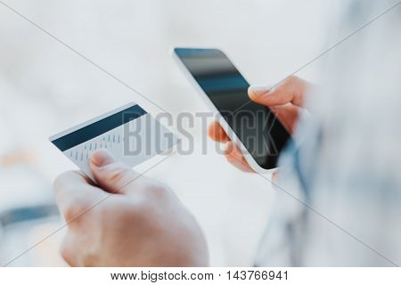 Closeup young man hands holding credit card and using cell, smart phone for online shopping or reporting lost card, fraudulent transaction