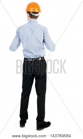 Backview of an engineer in construction helmet stands. Standing young guy. Rear view people collection.  backside view of person.  Isolated over white background. Curly businessman in a light jacket