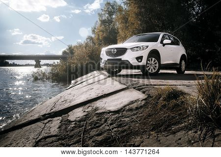Saratov, Russia - August 30, 2014: Car Mazda CX-5 stand on asphalt countryside road near river at daytime