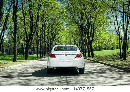 Moscow, Russia - May 07, 2015: Car Opel Insignia stand on asphalt road in green forest at daytime