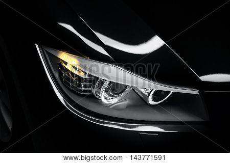 Headlight lamp of black modern car close-up