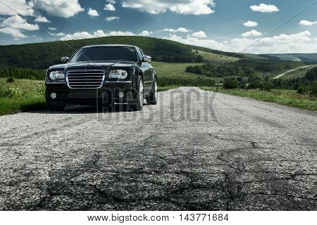 Saratov, Russia - August 9, 2015: Black car Chrysler 300c standing on asphalt road in the city at daytime