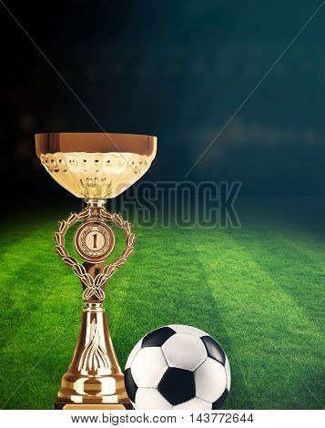 Trophy cup and soccer ball on football field stadium at night