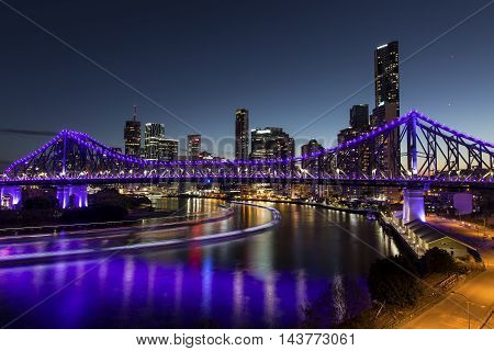 BRISBANE, AUSTRALIA - AUGUST 21 2016: Story Bridge at blue hour with light trails from the Brisbane City Cat ferries - purple lights