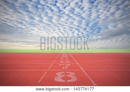 Athletic track lane number with Running track green grass and blue sky white cloud background