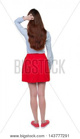 back view of standing young beautiful  woman.  girl  watching. Rear view people collection.  backside view of person. Long-haired brunette in red skirt straightens hair.