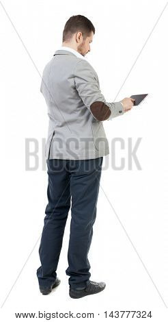 back view of business man uses mobile phone.    rear view people collection. Isolated over white background. backside view of person. The bearded man in a gray jacket click on the tablet screen.